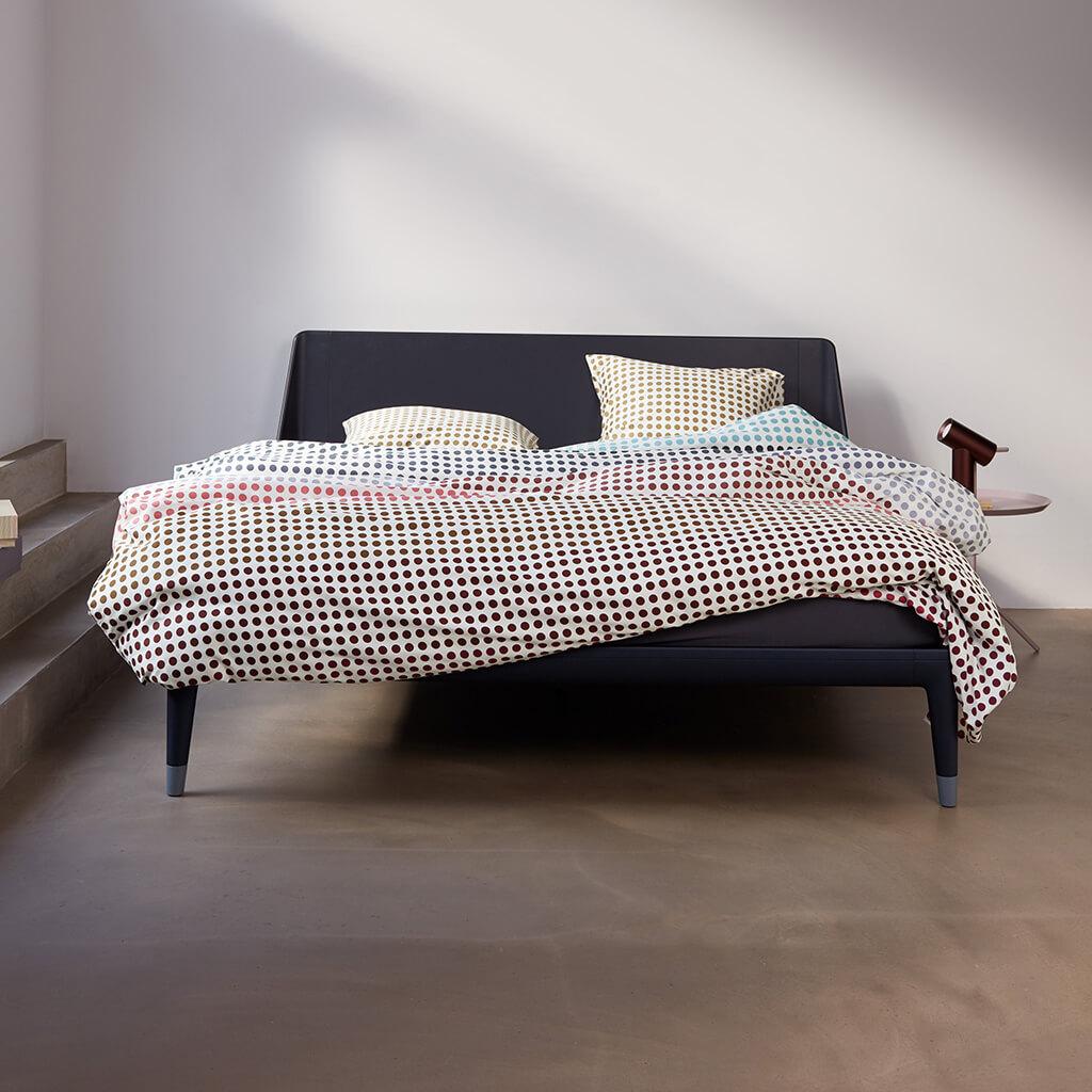 Vertigo dekbedovertrek multi op een Auping Essential bed
