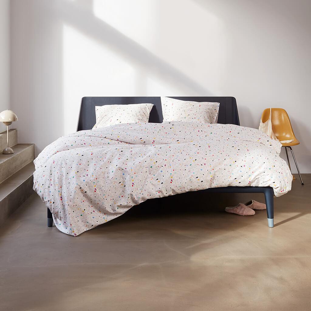Terrazzo dekbedovertrek multi op een Auping bed